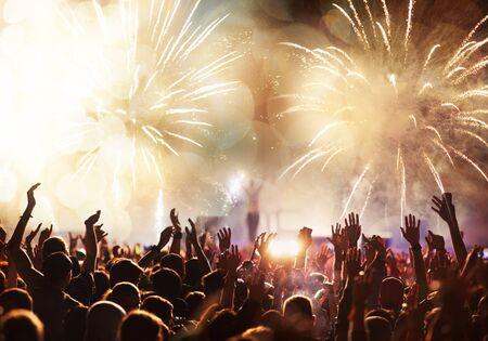 multitud con manos levantadas y banner de año nuevo de fuegos artificiales