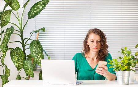 woman working in a green office laptop smartphone and tropical plants Foto de archivo
