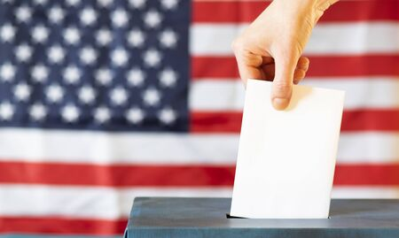 usa elections  the hand of woman putting her vote in the ballot box Stock Photo