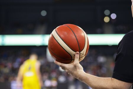 referee holding basketball during game