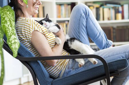 woman petting a cat at home