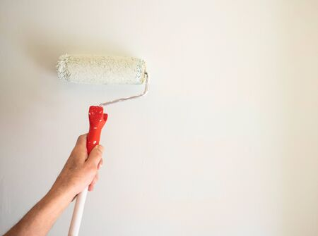 male hand painting wall with paint roller. Painting apartment, renovating with white color paint Imagens