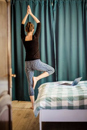 woman in a yoga pose in bedroom staying fit and mentally healthy at home
