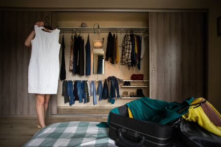 woman packing a suitcase trying on clothes wardrobe in background