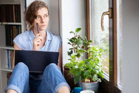 pensive woman working from home looking out on window
