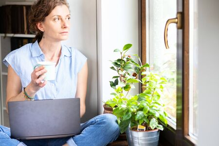 pensive woman working from home looking out on window thinking about future, relationship, career