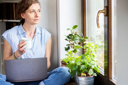 pensive woman working from home looking out on window thinking about future, relationship, career 免版税图像