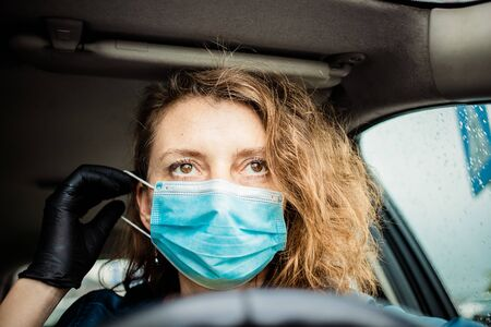 woman putting on medical mask in her car safety measures during pandemic