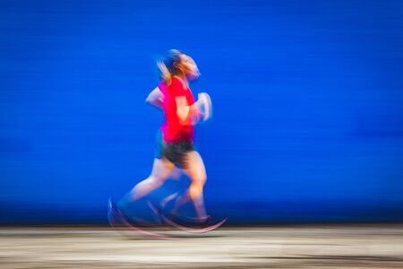 blurred image of woman jogging in a red shirt - healthy lifestyle