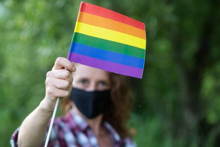 woman with mask holding rainbow flag   LGBT rights coronavirus