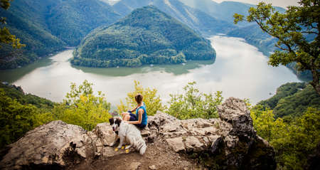 woman and dog on mountain top above lake Stock fotó