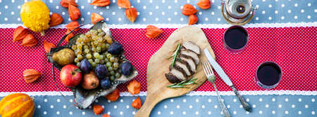 thanksgiving table with meat and fresh autumn fruits and vegetables Stock Photo