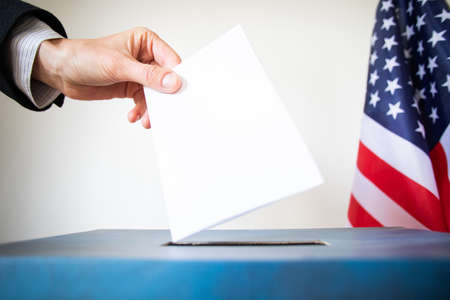 hand putting vote in ballot USA elections