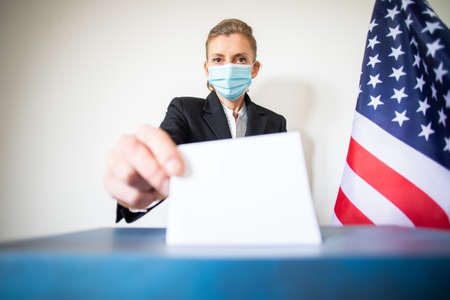 woman wearing mask putting vote in ballot