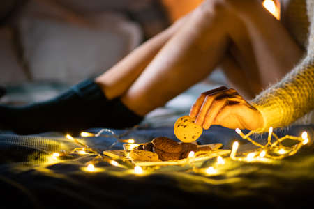 cozy Christmas at home woman in wool socks in bed eating cookies Stock Photo