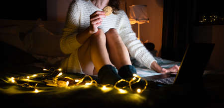 cozy Christmas at home woman wearing wool socks in bed with laptop Stock Photo