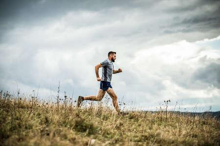 handsome trail runner running in nature