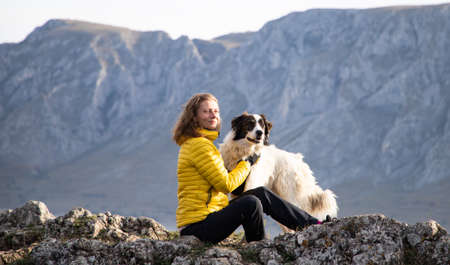 woman on mountain top with dog social distancing