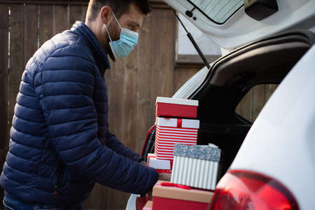 man packing Christmas gift boxes in car