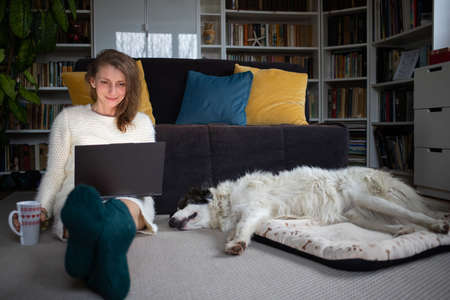 woman using laptop at home with dog hygge