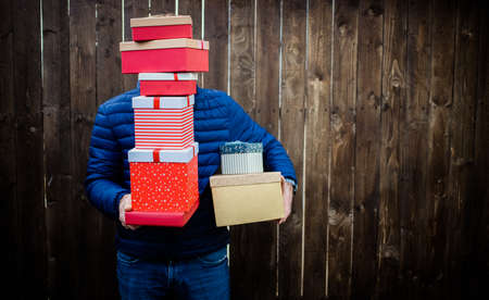 man holding pile of Christmas gift boxes