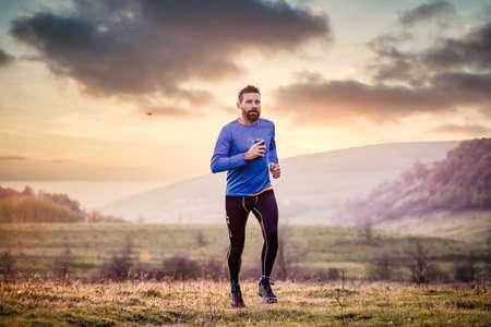 trail runner running on hill at sunset Imagens
