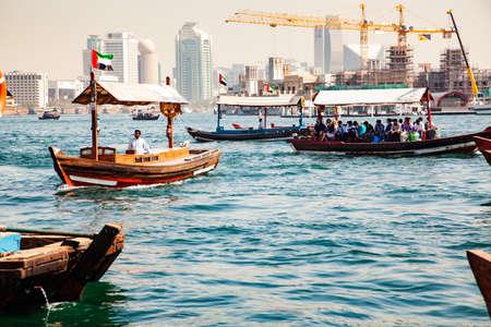 DUBAI, UAE- FEBRUARY 2018: Traditional Abra ferries crossing Dubai Creek. The Creek divides the city into two main sections: Deira and Bur Dubai