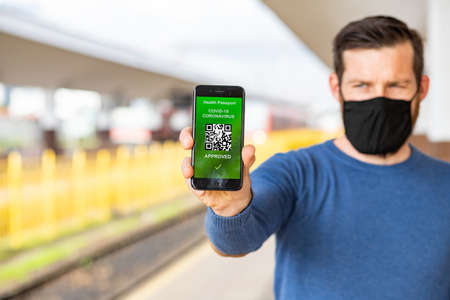 health Vaccine Passport for Coronavirus or Covid-19. Traveller Using Mobile Phone with Vaccination in Immune Status to Certificated International Traveling in train station