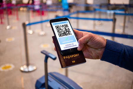 health Vaccine Passport for Coronavirus or Covid-19. Traveller Using Mobile Phone with Vaccination in Immune Status to Certificated International Traveling in Airport