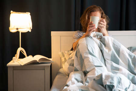 woman with coffee or tea cup in bed night time rest Foto de archivo