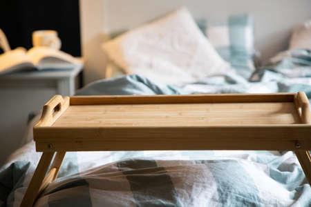 cozy bedroom detail focus on wooden breakfast tabletop