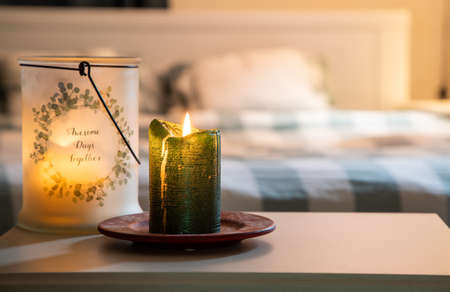 cozy bedroom detail focus on burning candle