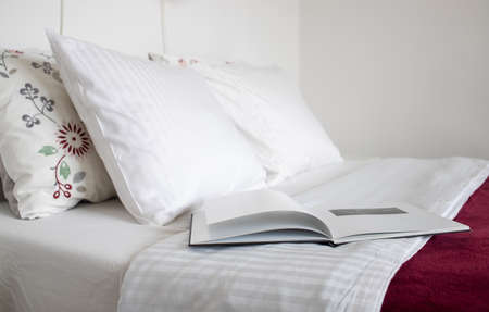 clean white pillows and open book on bed