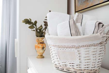 clean towels in a basket in hotel room Foto de archivo
