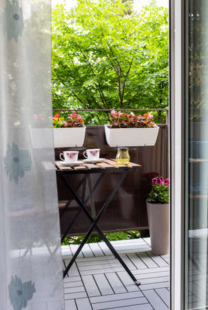 bright small apartment terrace in summer with flowers and coffee table