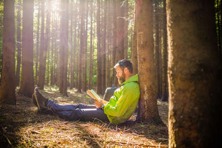 man reading a book in forest