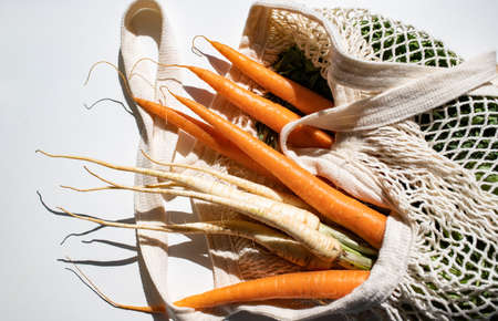 bunch of fresh carrots and parsley in an eco bag. Zero waste, plastic free concept. Sustainable lifestyle. Reusable cotton and mesh eco bags for shopping Foto de archivo