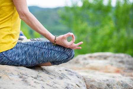 woman meditating in lotus pose on a rock in summer