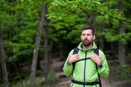 man trekking in green forest