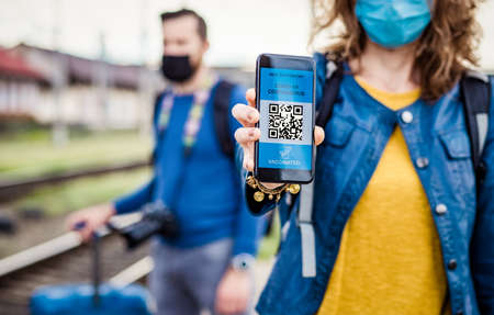 health Vaccine Passport for Coronavirus or Covid-19. Traveller Using Mobile Phone with Vaccination in Immune Status to Certificated International Traveling in train station Foto de archivo