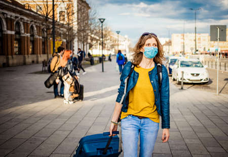 woman traveler with suitcase wearing mask