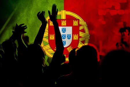 football fans supporting Portugal - crowd celebrating in stadium with raised hands against Portugal flag