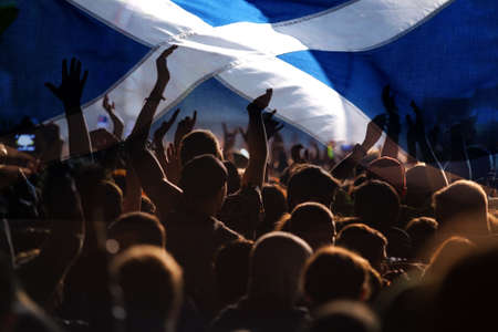 football fans supporting Scotland - crowd celebrating in stadium with raised hands against Scotland flag