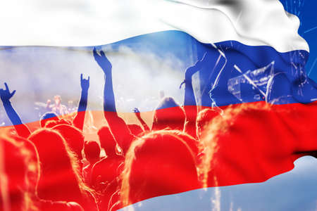 football fans supporting Russia  - crowd celebrating in stadium with raised hands against Russia flag Foto de archivo