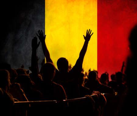 football fans supporting Belgium - crowd celebrating in stadium with raised hands against Belgium flag