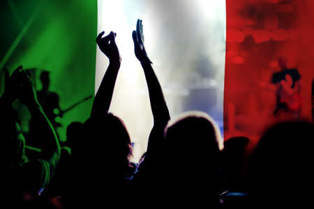 football fans supporting Italy - crowd celebrating in stadium with raised hands against Italy flag Foto de archivo