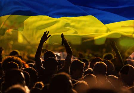 football fans supporting Ukraine - crowd celebrating in stadium with raised hands against Ukraine flag