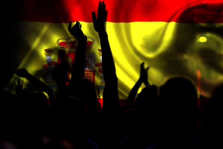 football fans supporting Spain- crowd celebrating in stadium with raised hands against Spanish flag