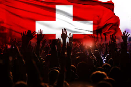 football fans supporting Switzerland - crowd celebrating in stadium with raised hands against Switzerland flag