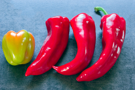 dissimilarity: Peppers - three identical and one different in color and shape.concept of difference.